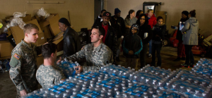 Residents of Flint lined up on Friday to get cases of bottled water distributed by members of the Michigan National Guard. Credit Brittany Greeson for The New York Times